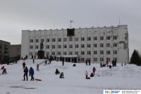 Дети катаются на санках у здания администрации